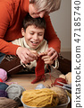 Mother is learning her child boy to knit.  47185740