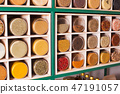 Collection of glass jars with spices on wooden stand 47191057