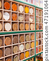 Wooden rack with cells filled with spices in jars 47191064