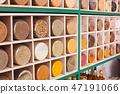 Close view of spices in glass jars on wooden shelf 47191066