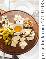 Cheese plate with hazelnuts, honey, grapes on wooden table 47191085
