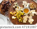 Cheese plate with hazelnuts, honey, grapes on wooden table 47191087