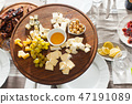 Cheese plate with hazelnuts, honey, grapes on wooden table 47191089