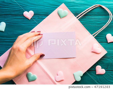 Pink blank card on shopping bag with hearts 47191283