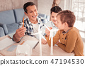 Dark-haired smiling man feeling very happy with his sons 47194530