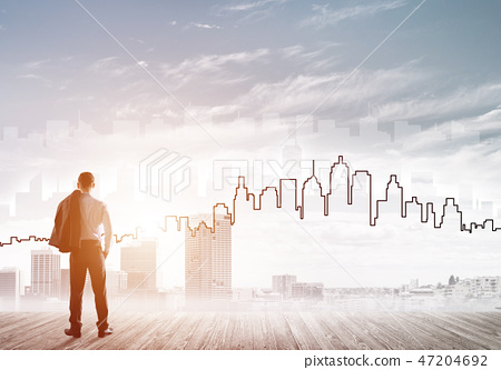 Motivation and inspiration concept with modern cityscape and businessman observing it 47204692