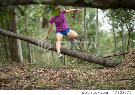 Sportswoman cross country trail running in forest 47208279
