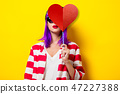 girl with purple hair holding heart shape 47227388