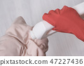Hand in glove pours liquid for washing on clothes 47227436