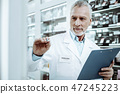 Attentive senior pharmacist working consciously in drugstore 47245223