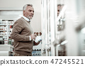 Caring husband coming to pharmacy store buying some vitamins for family 47245521