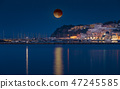 Total lunar eclipse above small seaside town 47245585