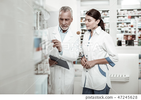 Bearded owner of drugstore giving some instructions while hiring new pharmacist 47245628