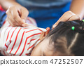 Parent help her child perform first aid ear injury 47252507