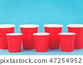 Red paper cups rows on blue background 47254952