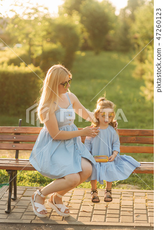Mom and his little daughter are sitting on a bench in the park 47260123