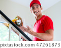 Delivery man holding flower bouquet 47261873