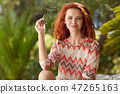 Beautiful young redhead in a summer meadow 47265163