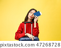 Woman travel. Young beautiful asian woman traveler with passport and suitcase on yellow background 47268728
