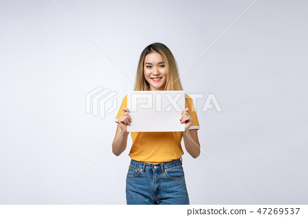 Excited woman showing empty blank paper card sign with copy space for text. Gorgeous multi ethnic 47269537