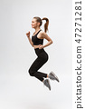 Full length picture of happy beautiful fitness woman over gray background 47271281