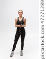 Sport woman. Young beautiful woman in sport clothes. Portrait full length sitting in headphones 47271289