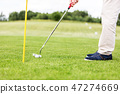 Golfer putting ball in the hole on a golf course. 47274669