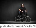 Smiling man with dreadlocks standing with his BMX 47274670