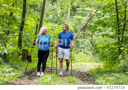 Elderly couple enjoying summer walk in the forest. 47274719