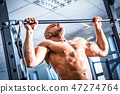 Muscular strong man training at a gym. 47274764
