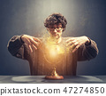 Young man gazing at the glowing crystal ball. 47274850