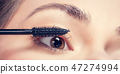 Young woman applying mascara to her lashes. 47274994