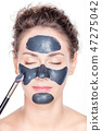 Black charcoal mask application on beautiful woman. 47275042