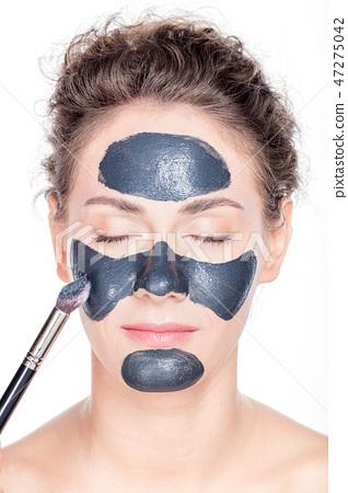 Black charcoal mask application on beautiful woman. 47275042