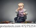 Baby boy examining a building block. 47275254