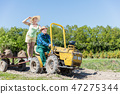 Grandfather taking grandmother for ride on tractor trailer across countryside 47275344
