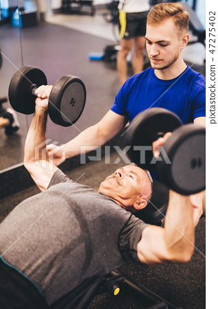 Personal trainer assisting older man in an exercise 47275402