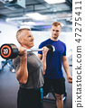 Senior man weightlifting, assisted by personal trainer. 47275411