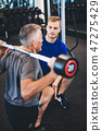 Personal trainer and senior man exercising at the gym. 47275429