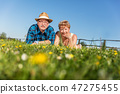 Senior couple lying on the summer field in green grass 47275455