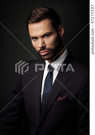 Handsome young businessman portrait on black background 47275597