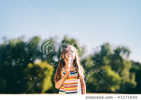 Little girl blowing soap bubbles in the park. 47275680