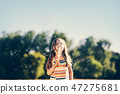 Little girl blowing soap bubbles in the park. 47275681