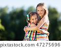 Two little girls hugging each other in the park. 47275696