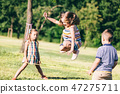 Little girl jumping through the elastic, playing with other children. 47275711