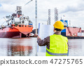 Shipbuilding engineer checking documents at the dock side in a port. 47275765