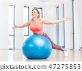 Cheerful woman training with fitball at fitness club. 47275853