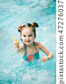 Girl in a swimming pool with a water pistol 47276037