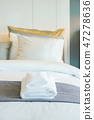 Clean white towels setting on bed in bedroom 47278636