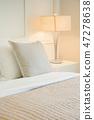Beige pillow on comfy bed in modern bedroom 47278638